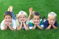 Four Children Laying in the Grass