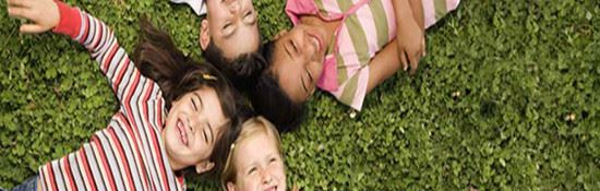Four Children Laying on Their Backs in the Grass.